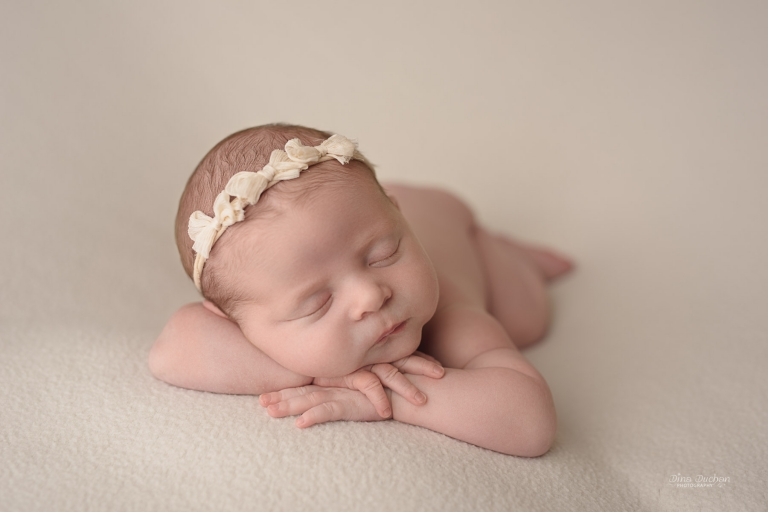 Newborn Lying Down Naked With A Bows Head Band