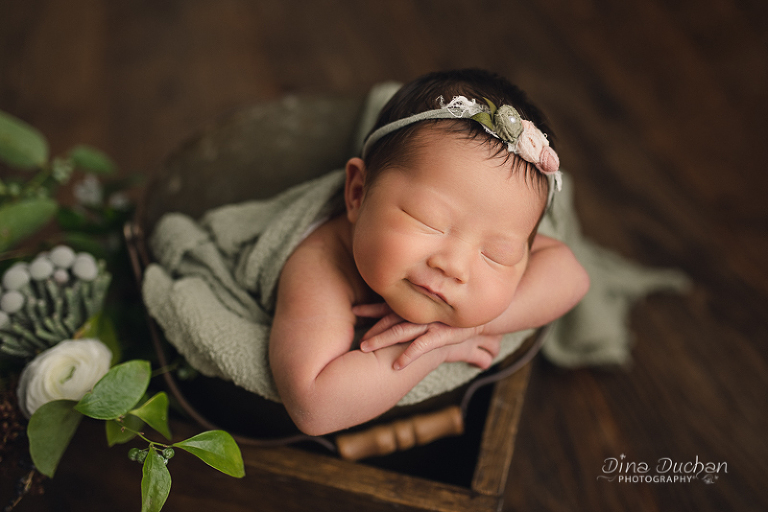 Brooklyn Newborn Photography baby smiling in crate with flowers